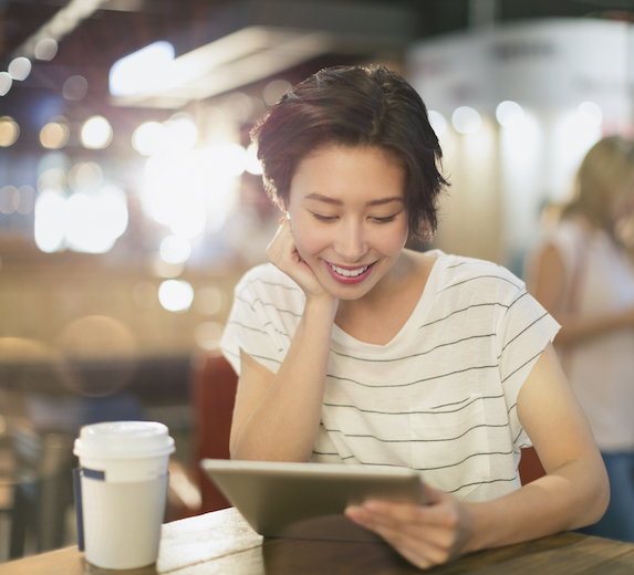 A young woman sits at a coffee shop with her digital tablet in hand