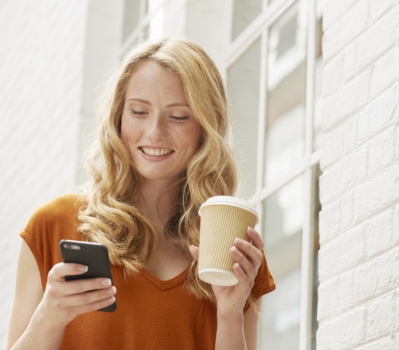 Smiling blonde woman looks down at the mobile phone in her hand