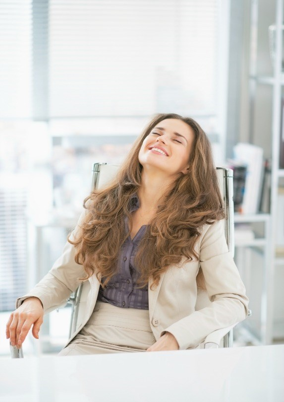 woman taking a deep breath at work
