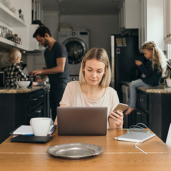 Woman working at kitchen table with family behind her