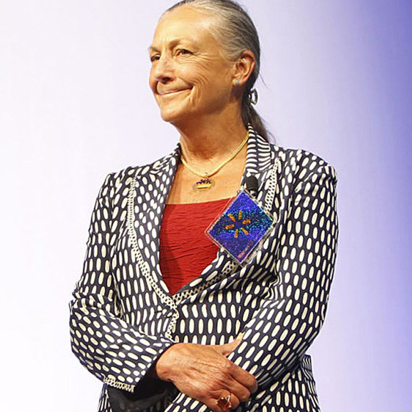 Alice Walton standing and smiling in a suit