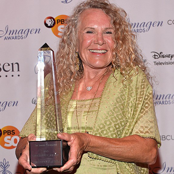 Christy Walton standing with a trophy and smiling euphorically
