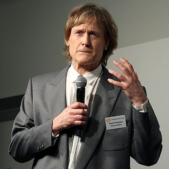 David Thomson mid-speech in gray suit