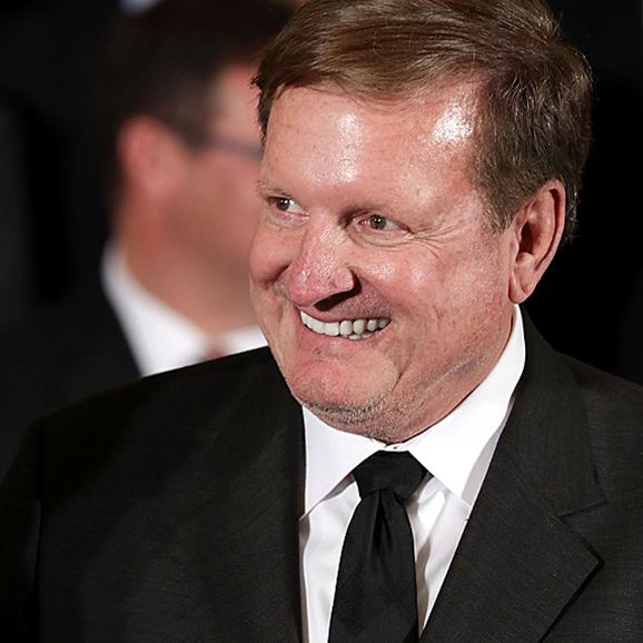 Ronald Burkle smiling in a suit and tie