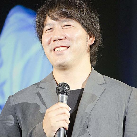 Yoshikazu Tanaka giving a speech and smiling