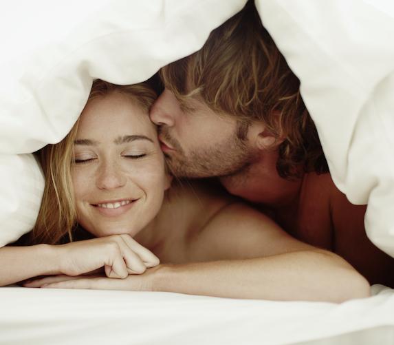 Couple cuddles under a blanket