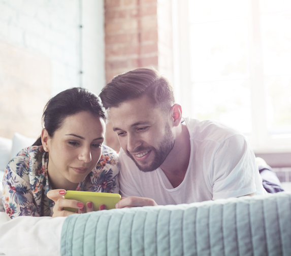 Couple uses cell phone in bed
