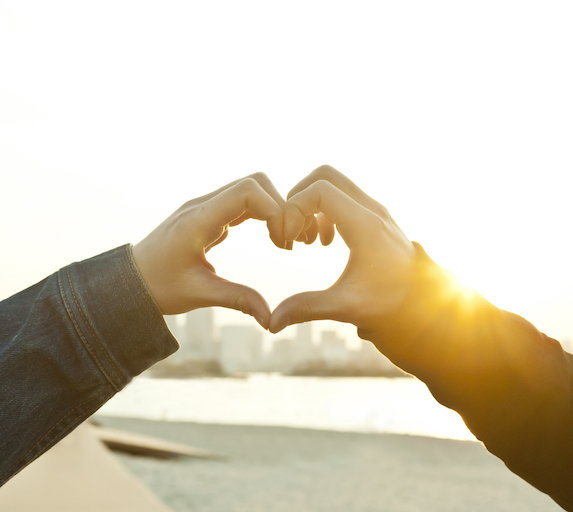 Couple makes heart symbol with hands