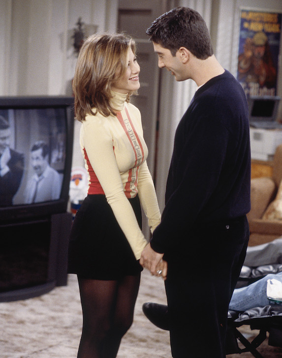 Jennifer Aniston, as character Rachel Green on 'Friends' wears a black mini skirt with dark stockings and a pastel yellow turtleneck