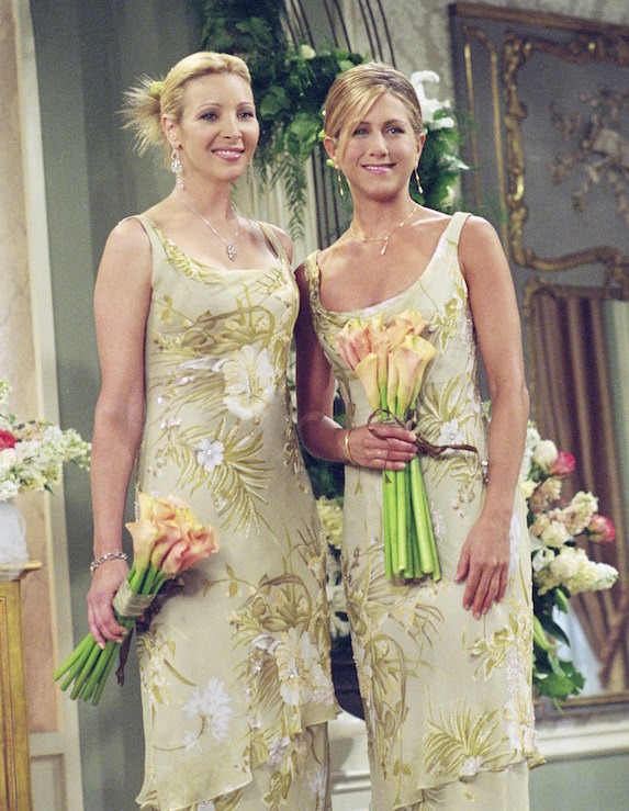 Jennifer Aniston, as character Rachel Green and co-star, character Pheobe on 'Friends', wear floaty yellow floral-print bridesmaid gowns