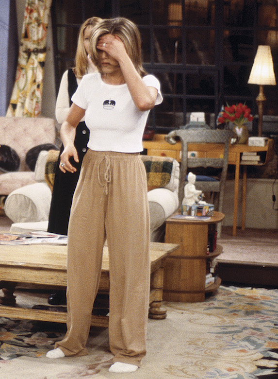 Jennifer Aniston, as character Rachel Green on 'Friends' wears loose-fitting beige trousers with a white-cropped t-shirt
