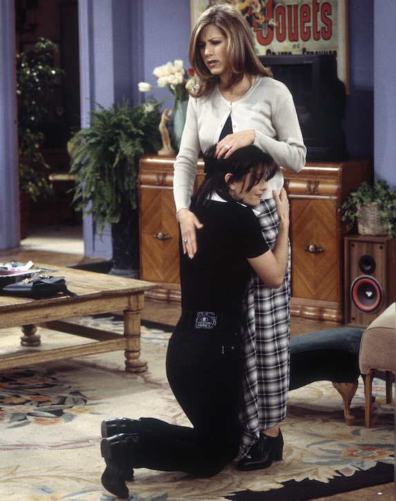 Jennifer Aniston, as character Rachel Green on 'Friends' wears a grey cardigan, black top and check-print pants
