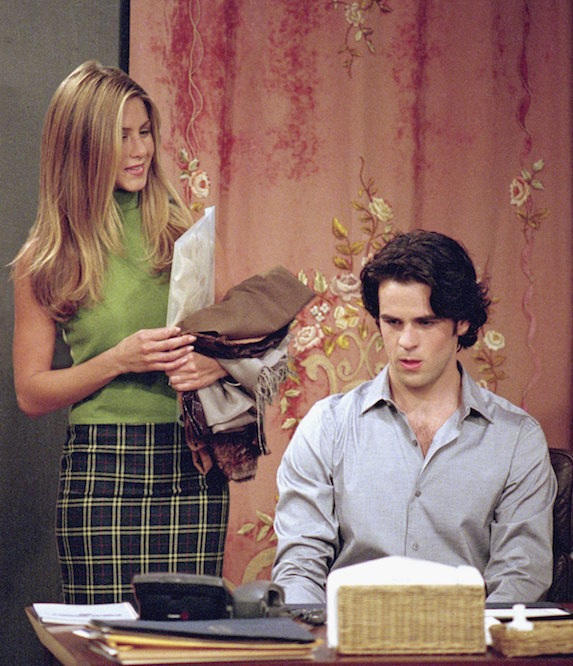 Jennifer Aniston, as character Rachel Green on 'Friends' wears a lime green sleeveless turtleneck and check pencil skirt