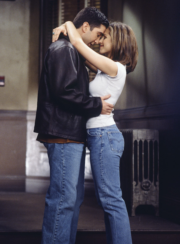 Jennifer Aniston, as character Rachel Green on 'Friends' embraces her co-star in a scene while wearing jeans and a white top