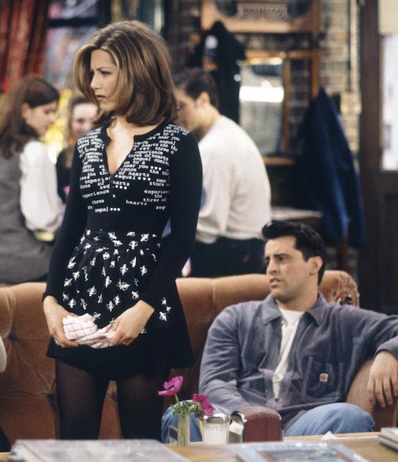 Jennifer Aniston, as character Rachel Green on 'Friends' wears a black mini skirt with stockings, apron, and black top