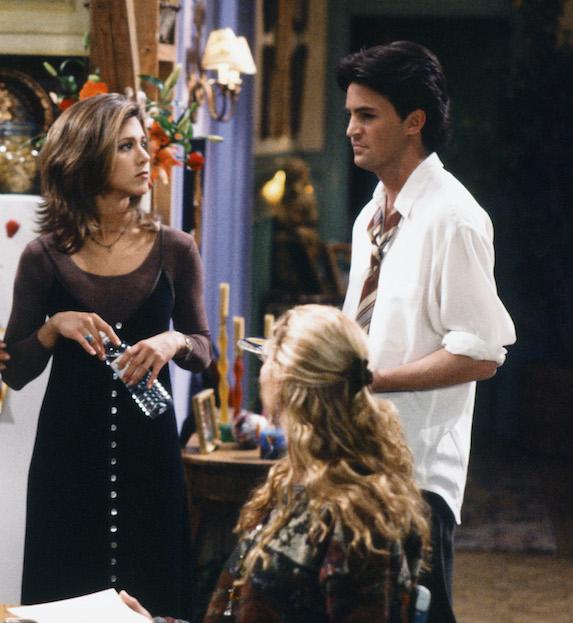 Jennifer Aniston, as character Rachel Green on 'Friends' wears a strappy dress over a long sleeve shirt