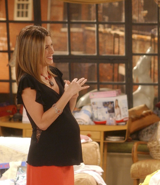 Jennifer Aniston, as character Rachel Green on 'Friends' sports a fake baby bump for her character's pregnancy, wearing a black short-sleeve blouse over a red skirt