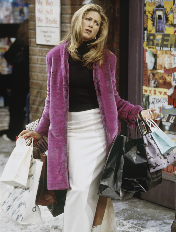 Jennifer Aniston, as character Rachel Green on 'Friends' wears a pink-purple faux fur coat over a black top and white maxi skirt