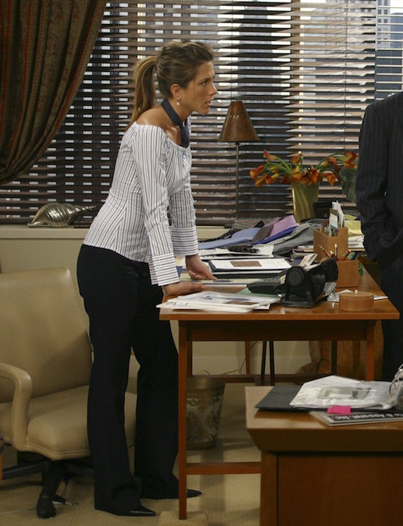 Jennifer Aniston, as character Rachel Green on 'Friends' wears a striped blouse and black pants while standing in her office