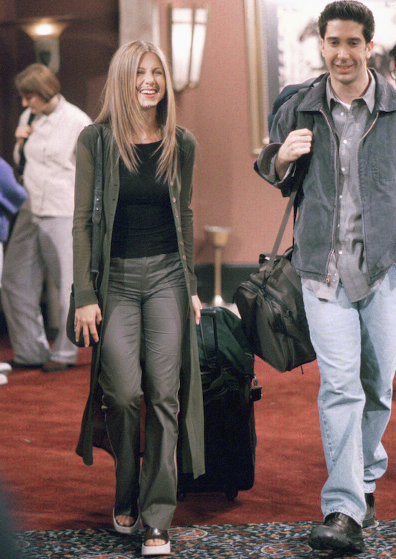 Jennifer Aniston, as character Rachel Green on 'Friends' wears platform shoes under casual pants, a black top and semi-sheer long over-shirt