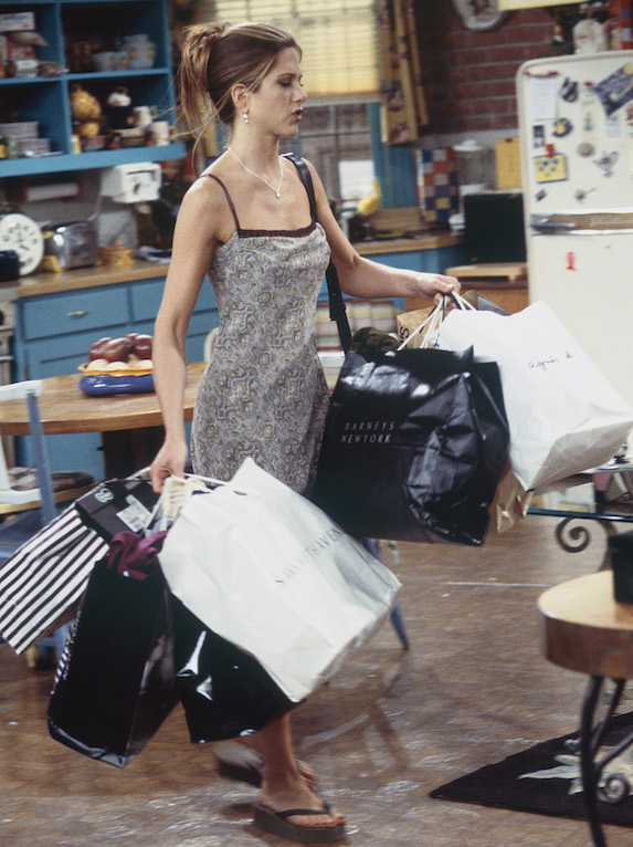 Jennifer Aniston, as character Rachel Green on 'Friends' carries shopping bags as she wears a simple slip dress and flip-flops