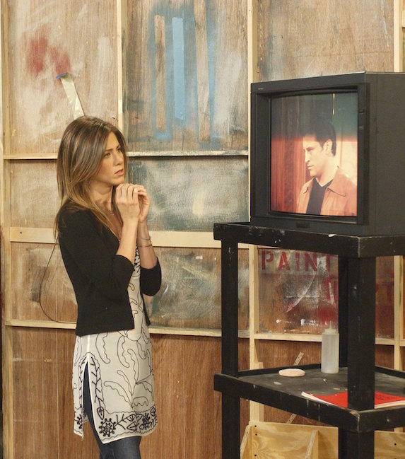 Jennifer Aniston, as character Rachel Green on 'Friends' wears a graphic tunic and cardigan over jeans