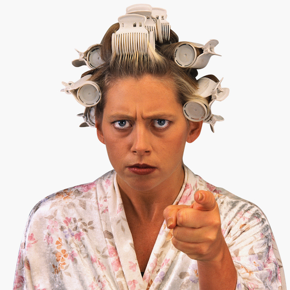 Woman with curlers in hair wearing bathrobe