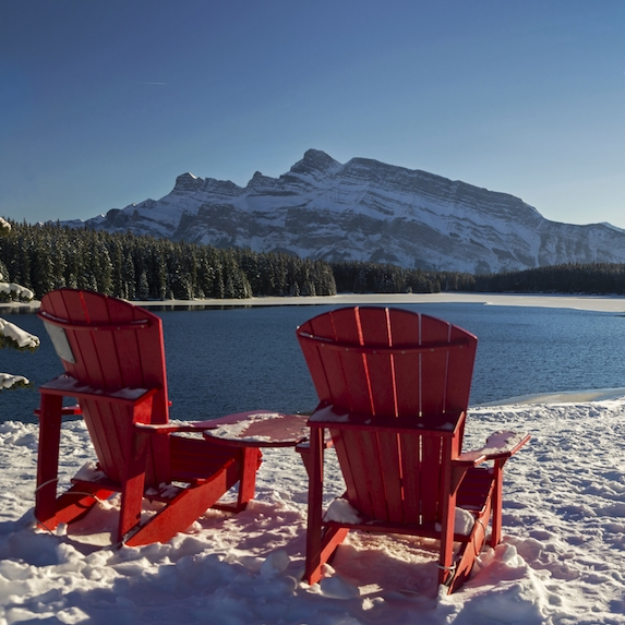 Red Adirondack Chairs and Distant Snowcapped Rocky Mountains Winter Landscape at Three Jack Lake in Banff National Park Alberta Canada