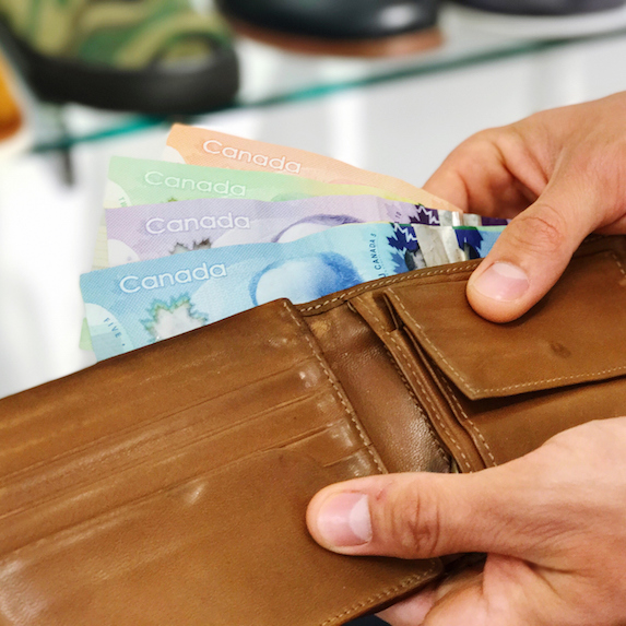 Hand removing Canadian money from wallet