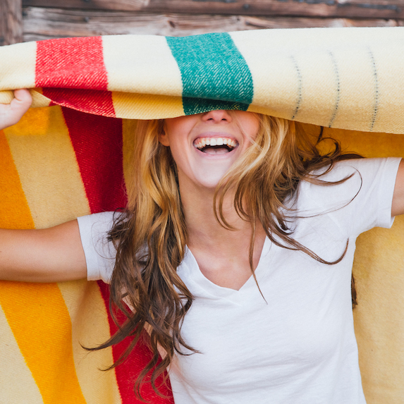 Woman laughing and holding Hudson Bay blanket covering her eyes