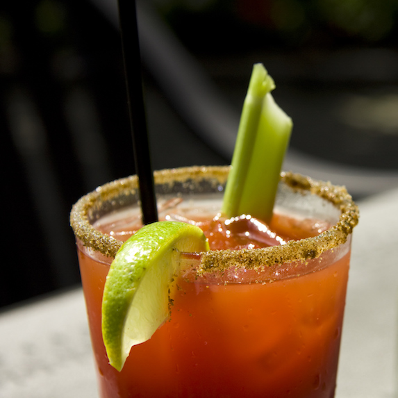 Close up of a caesar or bloody mary cocktail drink rimmed with spice and garnished with lime wedge and celery stick