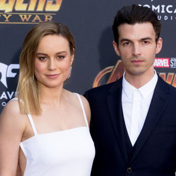 Brie Larson and Alex Greenwald standing side-by-side, posing for pictures
