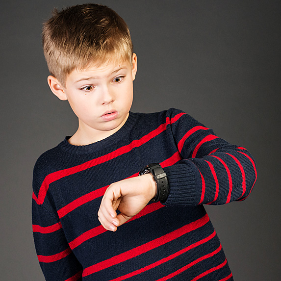 Boy looking at watch with bewildered look