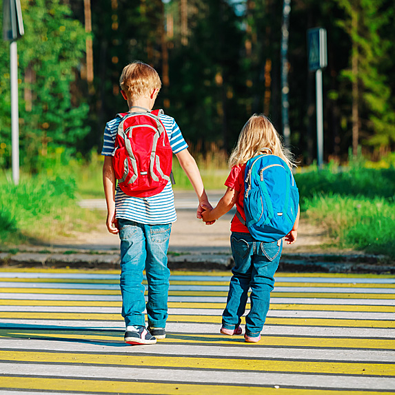 Boy holding girl's hand as they walk to school