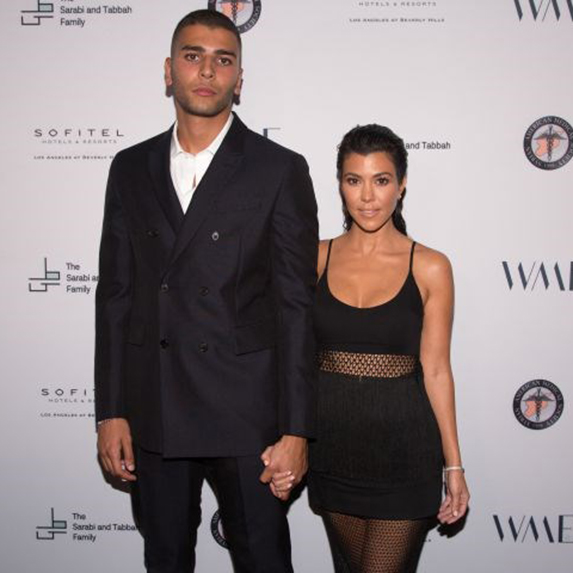 Kourtney Kardashian and Younes Bendjima at an event, dressed up