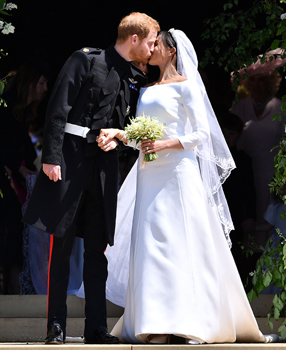 Britain's Prince Harry, Duke of Sussex kisses his wife Meghan, Duchess of Sussex as they leave from the West Door of St George's Chapel, Windsor Castle, in Windsor, on May 19, 2018 after their wedding ceremony