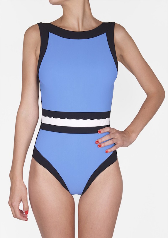 Model wears a colour-block one-piece swimsuit in blue, black and white