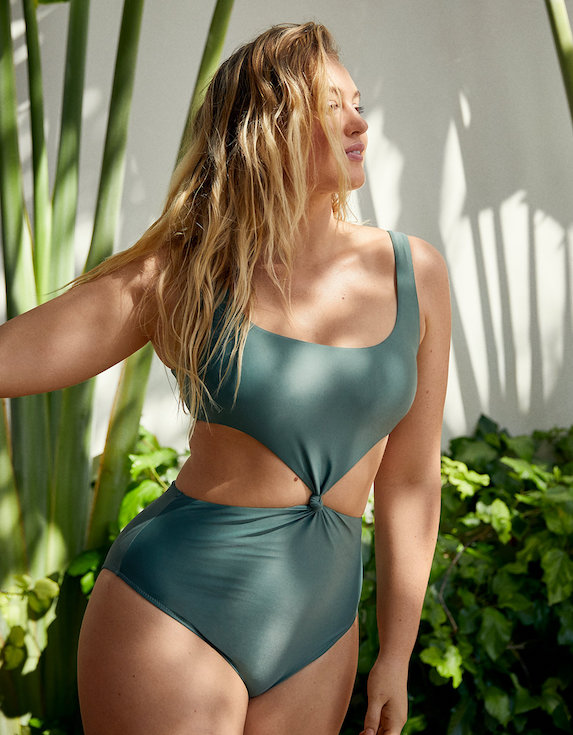 Model wears green swimsuit with cut-out details