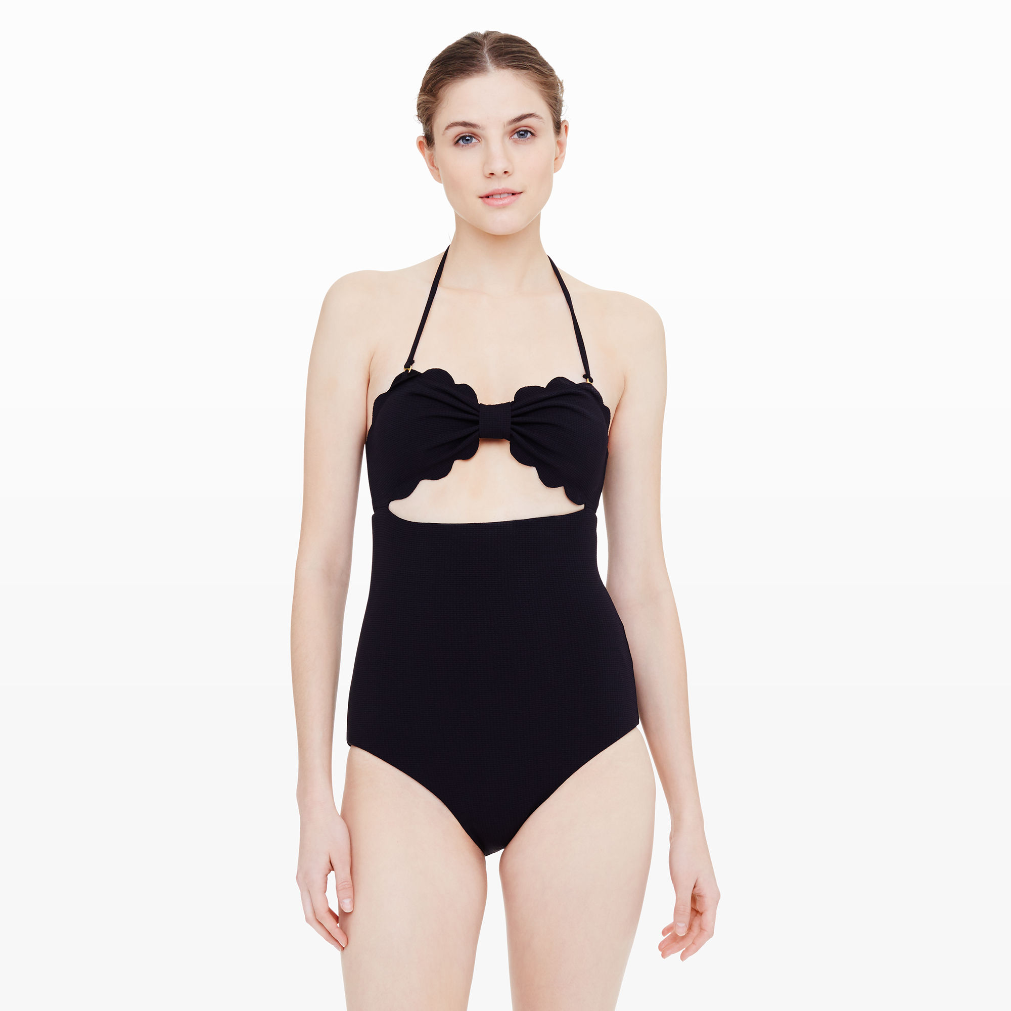 Model wears a black one-piece swimsuit with cut-out detail