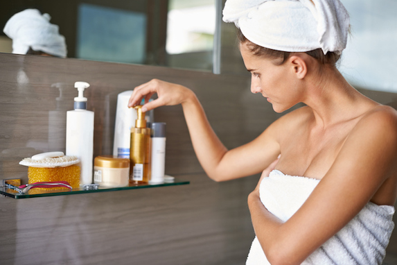 Shot of a woman wrapped on towels looking at bottles of cream in a bathroom