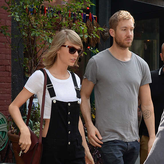 Taylor Swift and Calvin Harris walking outside in the summertime, mid-stride