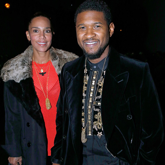 Usher and Grace Miguel walking together in jackets, smiling