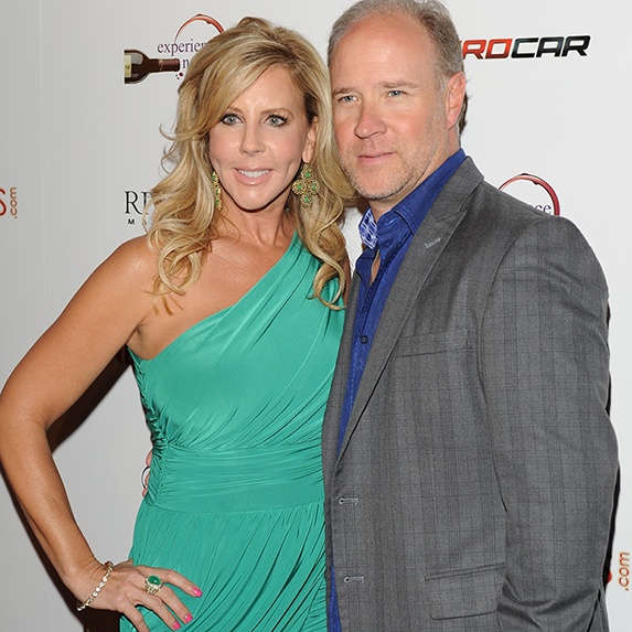 Vicki Gunvalson and Brooks Ayers leaning into each other and posing for the camera, dressed up