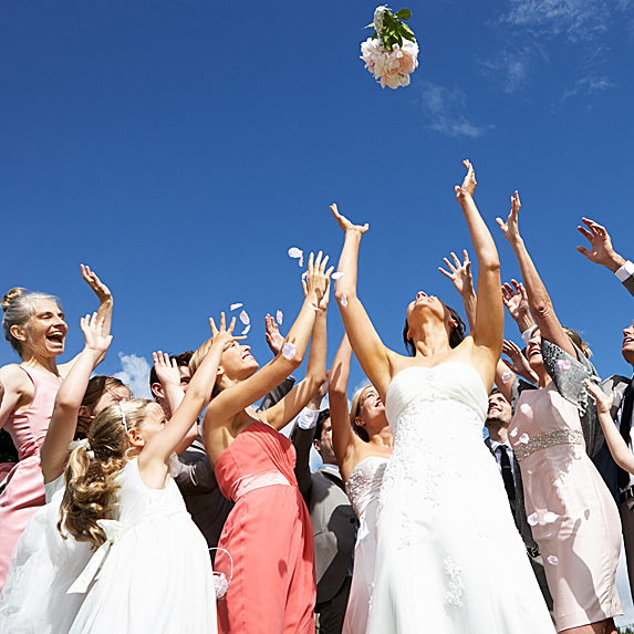 Bride tossing bouquet to crowd