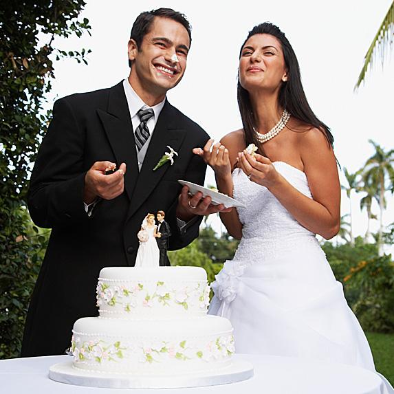 Groom and bride eating wedding cake