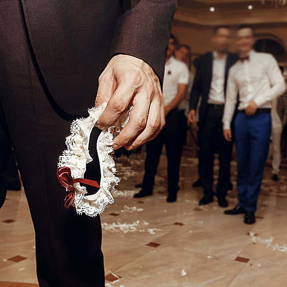 Closeup of groom's hand holding garter with men behind him