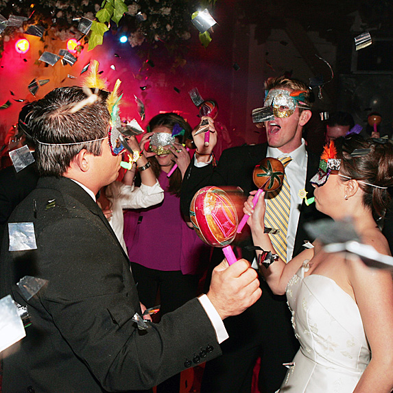Bride, groom and guests in masks on dance floor