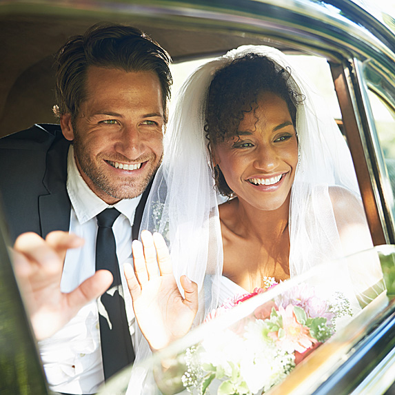 Groom and bride in car smiling out open window