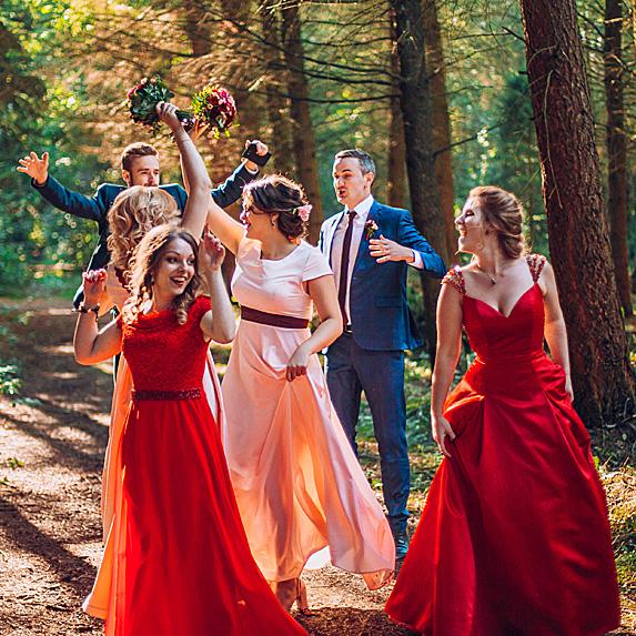 Wedding party dancing in woods