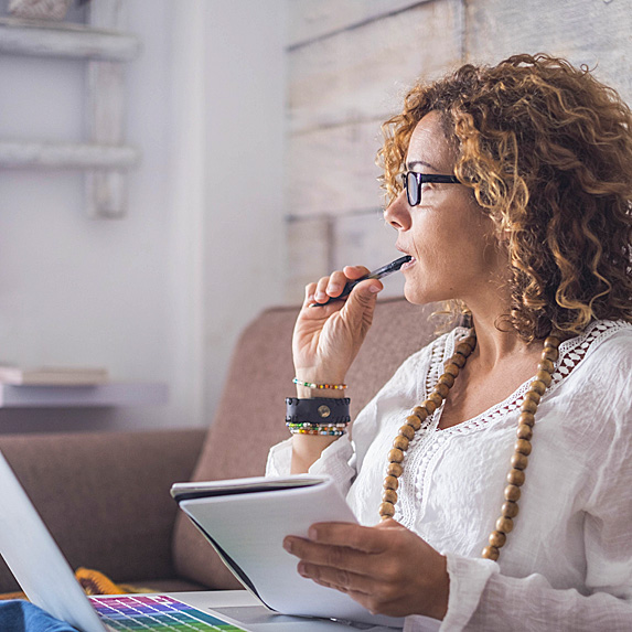 Concerned woman holding notepad with laptop open